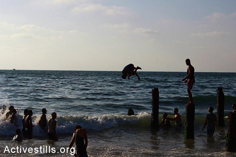 נערים קופצים מעמודי נמל ישנים, אשר נותרו על תילם, חוף עזה. (באזל יאזורי/אקטיבסטילס)