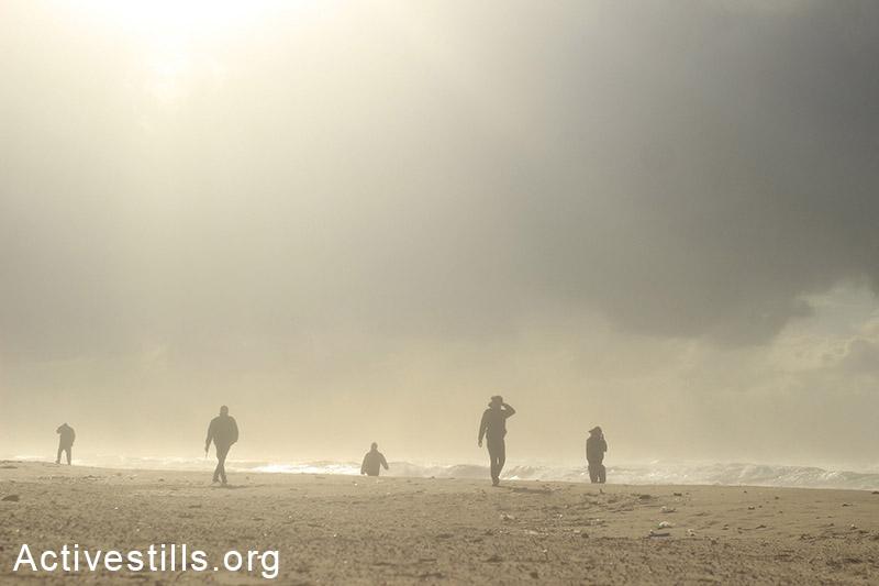 דייגים הולכים בסופה על חוף הים, בחזרה מעבודתם, חוף עזה. (באזל יאזורי/אקטיבסטילס)