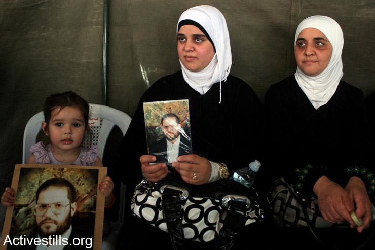 בנות משפחה של באהא יעיש מחזיקות את תמונתו באוהל מחאה בסולידריות עם אסירים פלסטינים, שכם, ה- 3 למאי, 2014. יעיש מוחזק 10 חודשים במעצר מנהלי בכלא הישראלי. יותר מ- 100 עצירים מנהליים המוחזקים בבתי כלא ישראלים החלו בשביתת רעב ב- 24 לאפריל לאחר שישראל חזרה בה מהבטחתה לפלסטינים להגביל את השימוש במעצרים מנהליים למקרים חריגים. (אקטיבסטילס)