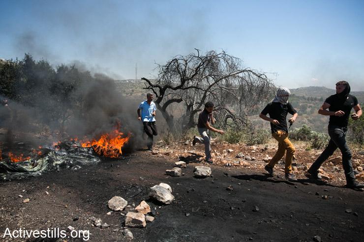 צעירים פלסטינים רצים ליד בריקדה במהלך הפגנה נגד הכיבוש בכפר קדום, ה- 2 למאי, 2014. (אקטיבסטילס)