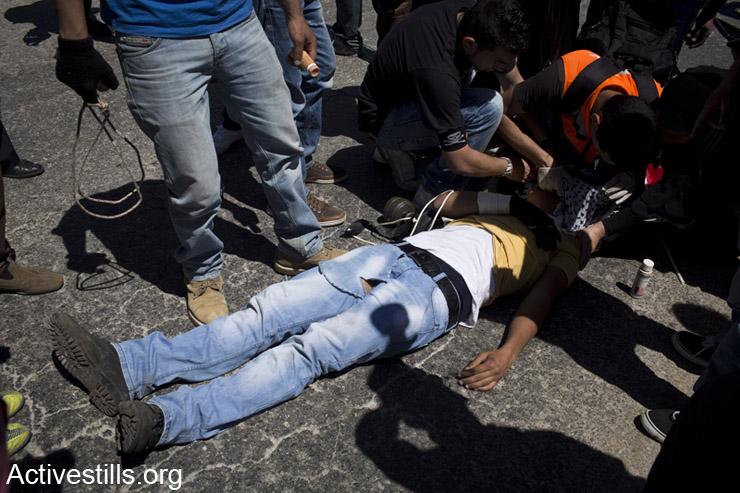 """פצוע פלסטיני שרוע על הארץ לאחר שנורה ע""""י חייל ישראלי במהלך הפגנה נגד הכיבוש, נבי סאלח, ה- 2 למאי, 2014. (אקטיבסטילס)"""