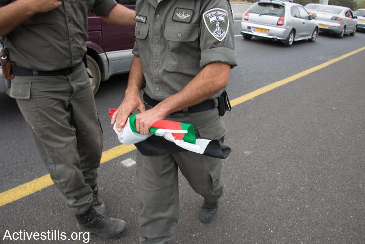 """שוטר מג""""ב מחזיק בדגל פלסטין שהחרים מאישה פלסטינית, אזרחית ישראל, שנופפה בו בדרכה לצעדת השיבה בכפר לוביה. ה-6 למאי, 2014. לוביה הוא אחד מ- 500 הכפרים הפלסטינים שנהרסו בנכבה. (אקטיבסטילס)"""