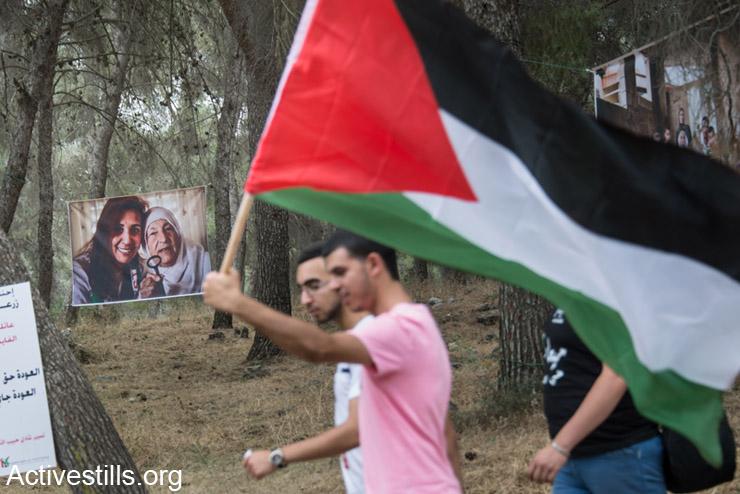 פלסטינים אזרחי ישראל צועדים ליד תמונות של פליטים פלסטינים במהלך תהלוכת השיבה לכפר לוביה, ה- 6 למאי, 2014. תהלוכת השיבה, המתקיימת באותו יום שבו נחגג בישראל יום העצמאות, מציינת את הנכבה הפלסטינית שבה נהרסו כ- 500 כפרים פלסטינים אשר תושביהם הפכו לפליטים. (אקטיבסטילס)