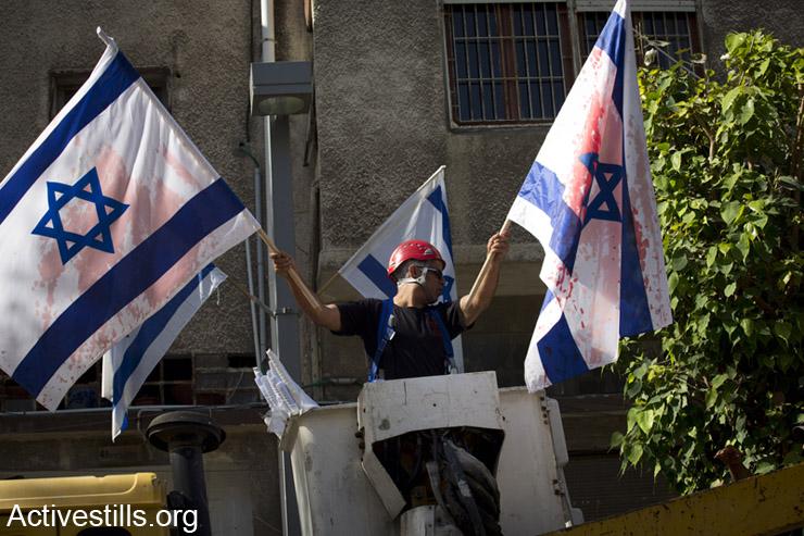 עובד של עיריית תל אביב מוריד דגלי ישראל, לאחר שלילה קודם נצבעו באדום, יפו, ה- 1 למאי, 2014. (אקטיבסטילס)