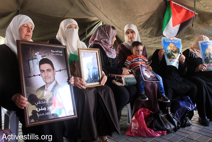 נשים פלסטינים מחזיקות תמונות של אסירים מנהליים באוהל מחאה שהוקם במרכז העיר שכם לתמיכה בשובתי הרעב (צילום: אקטיבסטילס)