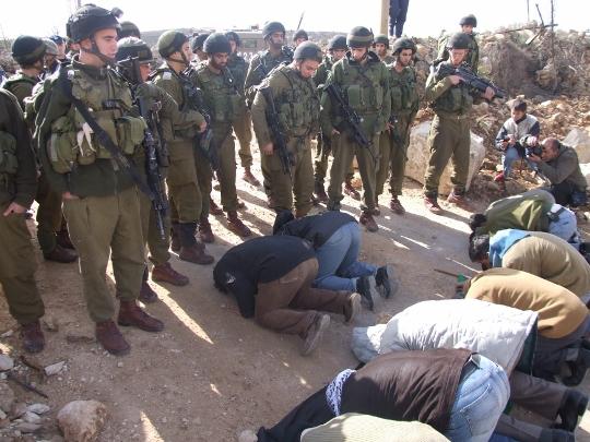מפגינים באל-מעסרה מתפללים לרגלי חיילים שמונעים מהם גישה לאדמותיהם (חגי מטר)