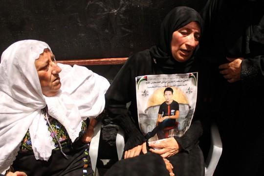 אמו וסבתו של מוחמד ג'יהאד דודין אוחזות בתמונתו הבוקר (צילום: עזאם תלאחמה)