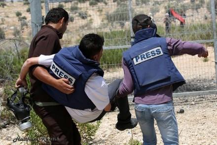 עיתונאי ומפגין מפנים את העיתונאי הפצוע (הייתאם אל-חטיב)