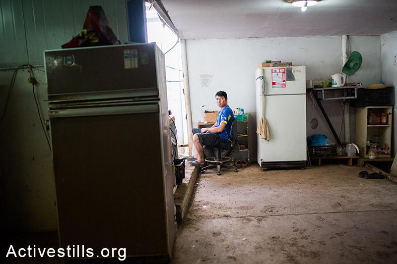 מושב פרזון, נובמבר 2013. עובד תיאלנדי יושב במגוריו. (יותם רונן/אקטיבסטילס)