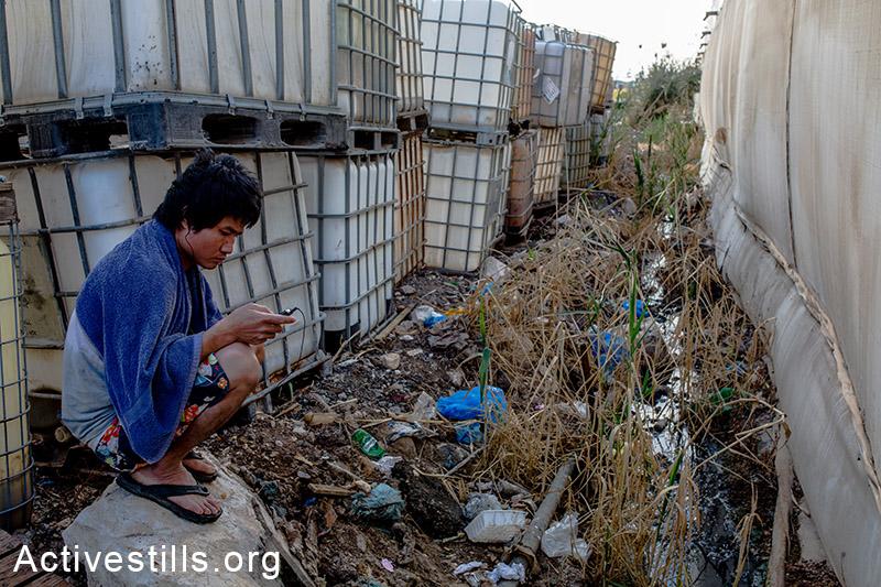 מושב פרזון, נובמבר 2013. עובד תיאלנדי יושב מאחורי מגוריו. (יותם רונן/אקטיבסטילס)