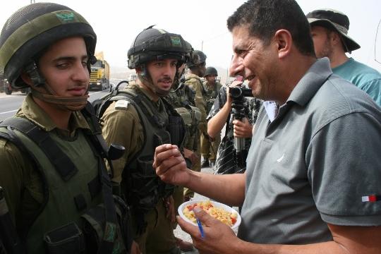 מחמוד זוואהרה מדבר עם חיילים בהפגנה לציון שש שנים להפגנות באל-מעסרה. המפגינים הציעו לחיילים פסטה (חגי מטר)