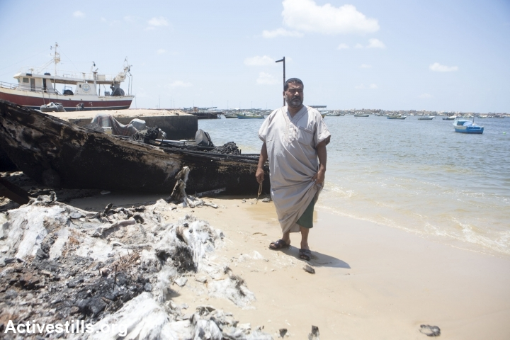 הדייג סאברי באחר, בן 53 ואב ל 16 ילדים, צועד לעבר סירתו ההרוסה בנמל עזה, 15 ביולי, 2014. בשנת 2012 הוחרמה סירתו הקודמת על ידי הצבא הישראלי ומעולם לא הוחזרה. הסירה נהרסה בזמן התקיפה הישראלית ב-11 ביולי 2014. (צילום: אן פאק/אקטיבסטילס)
