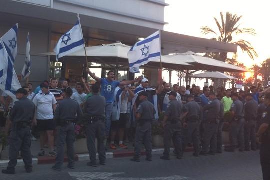 דבוקה של גברים עם דגלים והמנונים ותנועות ידיים, והמשטרה תוחמת אותם. (צילום: אביגיל שחם)