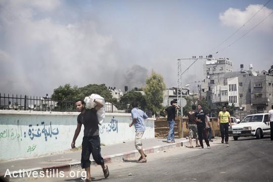 תושבים בורחים משג'עיה בעקבות פלישה של טנקים ישראלים לשכונה. הפצצות כבדות הביאו ל-60 הרוגים ומאות פצועים. עזה, 20 יולי 2014. (אן פאק/ אקטיבסטילס)