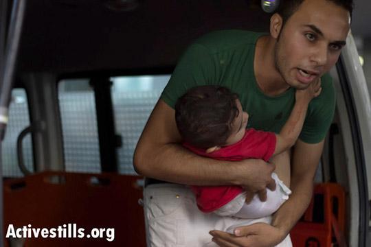 נער פלסטיני נושא תינוק שנפצע במהלך תקיפה ישראלית בעזה, בלילה של ה-8 ליולי, 2014. (באסל יאזורי/אקטיבסטילס)
