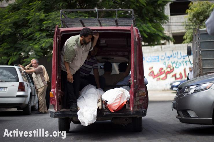 גופות בני משפחת אל-באטש מובלות אל חדר המתים של בית החולים אל-שיפא, עזה, ה-13 ליולי, 2014. התקפה ישראלית הרגה כ-18 מבני המשפחה. באסל יאזורי/אקטיבסטילס