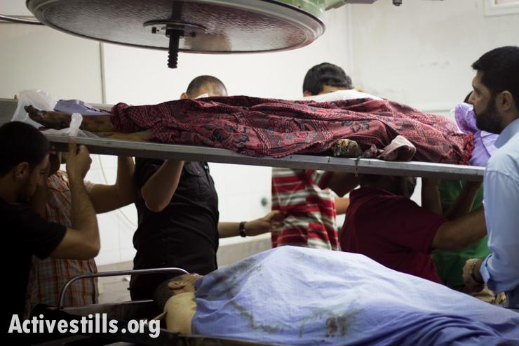 גופות בחדר המתים של בית החולים אל-שיפא, עזה, ה-13 ליולי, 2014. באסל יאזורי/אקטיבסטילס