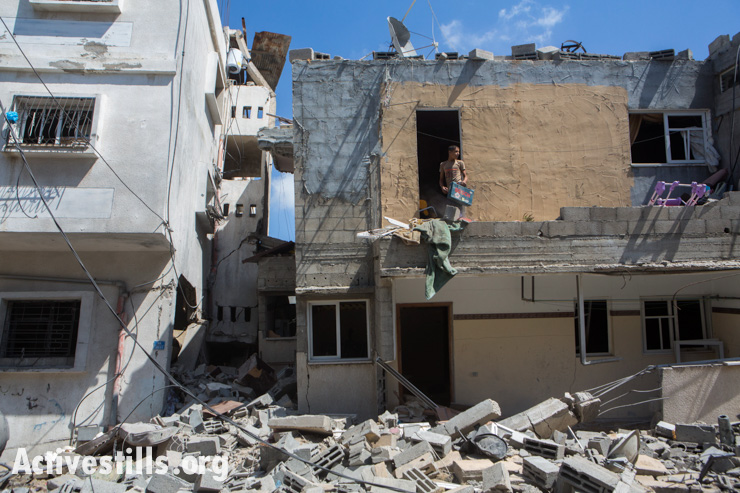 פלסטינים בודקים בית הרוס בו התגוררו בני משפחת אשטאווי באזור אז-זייתון שברצועה, עזה, ה-14 ליולי, 2014. אן פאק/אקטיבסטילס
