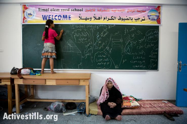 ילדה ממשפחת אל-טום מציירת על לוח בגיר בבית הספר היסודי של אונרווה שהוסב למקום מקלט עבור פליטים צפון-עזתיים שנסו מבתיהם לאחר התרעות הצבא, ה-13 ביולי, 2014. זו הפעם השלישית שהמשפחה בורחת מהתקפות ישראליות. אן פאק/אקטיבסטילס
