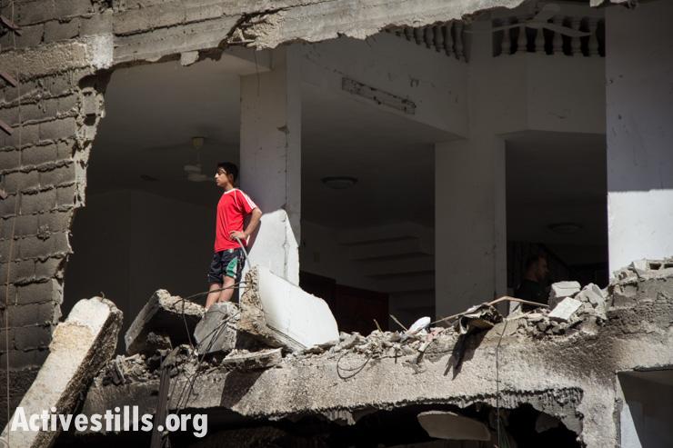 נער מתבונן על מבנה הרוס לאחר הפצצה ישראלית, עזה, ה-14 ליולי, 2014. אן פאק/אקטיבסטילס