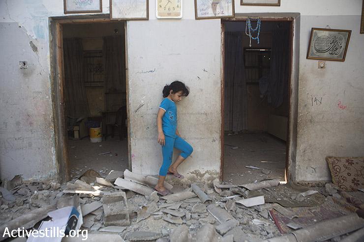 ביתו של דיאב בכר בין הריסות ביתה שהופצץ על ידי טילים ישראל לילה קודם. בית נוסף של משפחת בכר המורחבת נהרס כליל ואחר ניזוק בהפצצה. חסן חאדר בכר נהרג ברחוב בעת ההפצצה. מחנה הפליטים א-שאטי, עזה, 22 ליולי, 2014. (אן פאק/אקטיבסטילס)