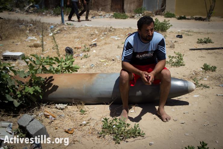 חאסם שאמדי יושב על טיל ישראלי שלא התפוצץ לאחר התקפה אווירית בשכונת תל אל-האווה, עזה, ה-14 ליולי, 2014. באסל יאזורי/אקטיבסטילס