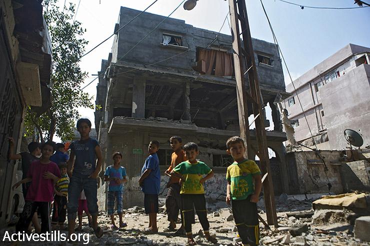 ילדים ממשפחת בכר המורחבת עומדים מחוץ לבתיהם ההרוסים במחנה הפליטים א-שאטי, בעיר עזה, 22 ביולי 2014. בני הדודים שלהם שגרים באותו האזור  עאהד (10), זכריא (10), מחמד (11) ואסמאעיל (9) נהרגו על ידי התקפות ישראליות בעת ששחקו על חוף הים, ב-16 ביולי 2014. (אן פאק/אקטיבסטילס)