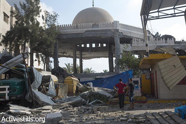 פלסטינים עומדים מול הריסות מסגד 'חללי אל אקצה' שהופצץ לילה קודם. עזה, 22 ביולי 2014. (אן פאק/אקטיבסטילס)