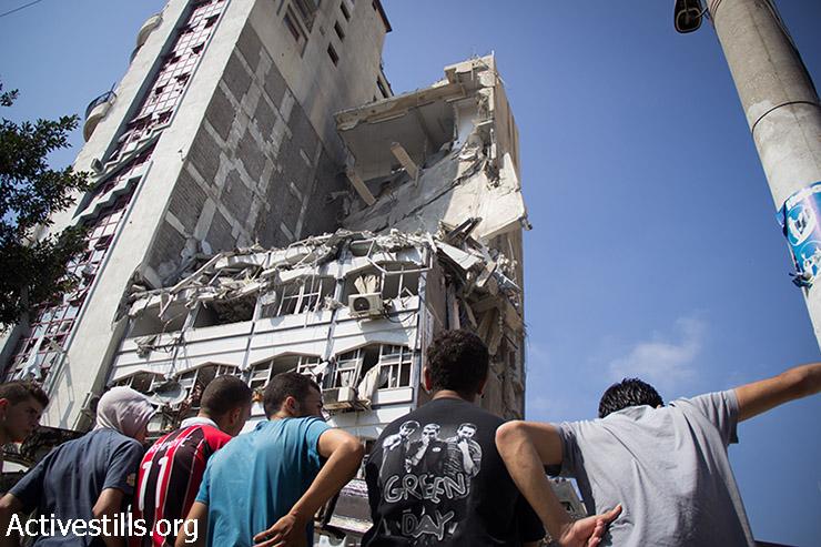 מגדל המגורים 'ישרא' ההרוס. הבניין נפגע משני טילים ישראליים לילה קודם שגרמו לקריסתו של מחצית מהבניין ולמותם של לפחות 12 פלסטינים. הכבאים הפלסטיניים עבדו במשך שעות כדי לחלץ את הגופות מתחת להריסות. עזה, 22 ביולי 2014. (באסל יאזורי/אקטיבסטילס)