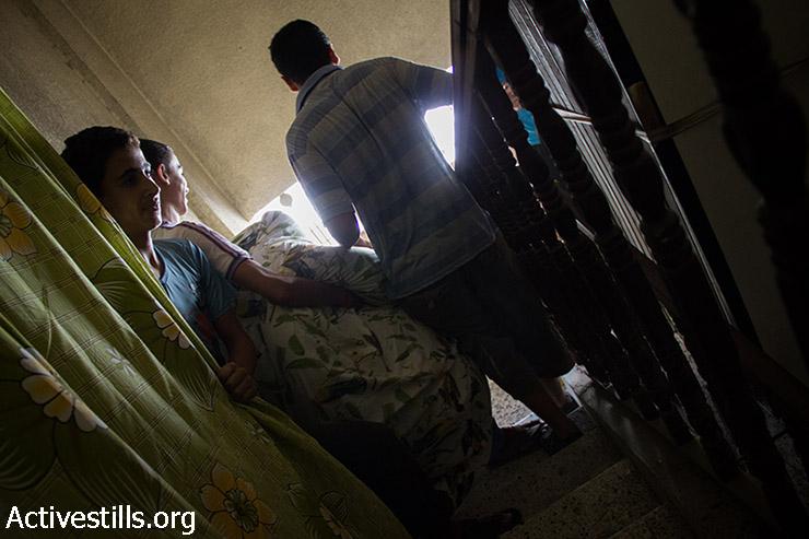 תושבים מפנים את ביתם לאחר שהבניין בו התגוררו ניזוק קשות בהפצצה אוירית על שכונת סברה. עזה, 22 ביולי 2014. (באסל יאזורי/אקטיבסטילס)