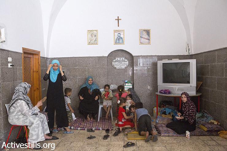 """פלסטיניות יושבות בתוך כנסיית סנט-פורפיריוס במרכז העיר עזה, בה הן מוצאות מפלט.אונר""""א מדווח על מעל 110,000 פלסטינים עקורים אשר מוצאים מקלט בבתי הספר של הארגון, אך המספר הכולל הוא ככל הנראה גבוה בהרבה. 22 ביולי 2014. (אן פאק/אקטיבסטילס)"""