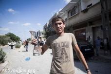 תושב עזה מציג חתיכה מטיל ישראלי בכפר עבאסן. 26 ביולי, 2014. (אן פאק / אקטיבסטילס)