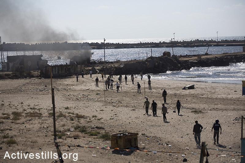 פלסטינים רצים לחלץ ארבעה ילדים שנהרגו מירי הצבא על אזור נמל עזה. הילדים, בני אותה משפחה, בחוף ונורו בפגיעה ישירה. ה-16 ליולי, 2014. (אן פאק/אקטיבסטילס)