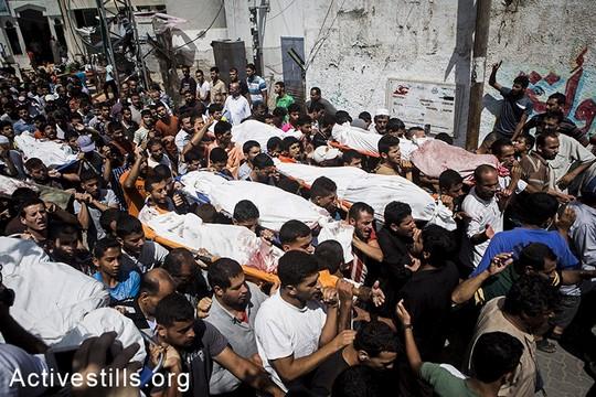 הלווייתם של 21 בני משפחת אלנג'אר שנהרגו זמן קצר לפני הפסקת האש, בכפר בני סוהילא, מזרחית לח'אן יונס,. 26 ביולי, 2014.