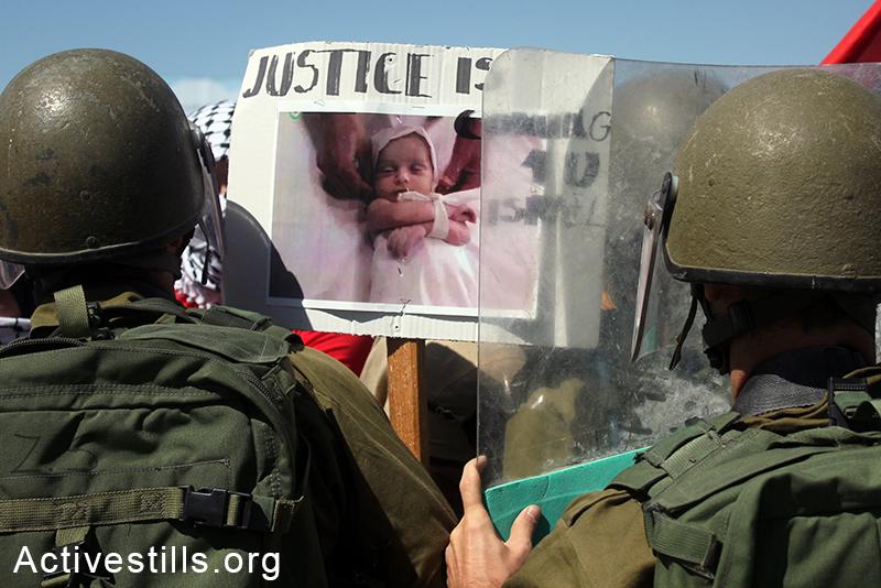 פלסטינים מפגינים נגד ההתקפה הישראלית בעזה, מחזיקים בידיהם תמונות של תינוקות וילדים שנפגעו בהפצצות, מחסום חווארה ליד העיר שכם, הגדה המערבית, ה-14 ליולי, 2014. אחמד אל-באז/אקטיבסטילס