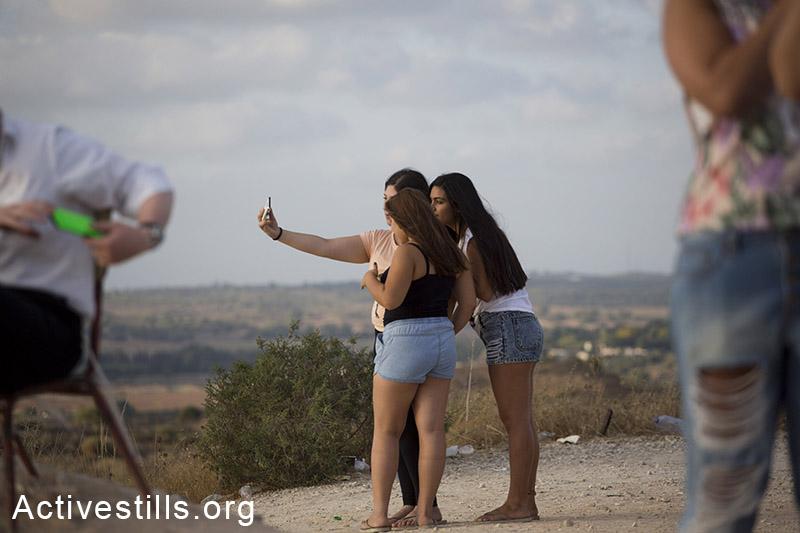סלפי על רקע שיגורי טילים לישראל ופיצוצים בעזה, ה-15 ליולי, 2014. אורן זיו/אקטיבסטילס