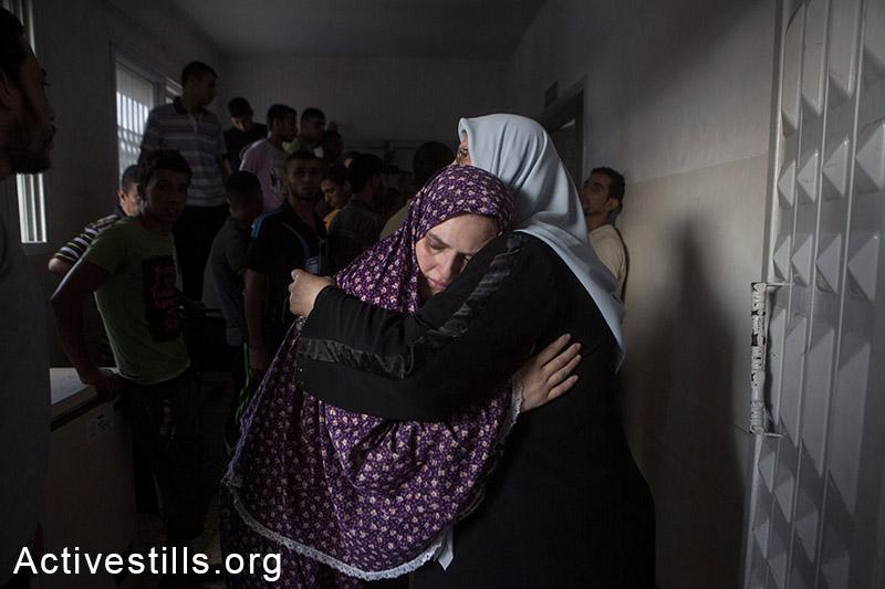 אימם של ג׳האד איסם שוהיבאר (8) ואאוסים איסם שוהיבר (7) מתאבלת על מותם של בניה שנהרגו בהתקפה ישראלית על שכונת סברה. עזה, ה-17 ליולי, 2014. (אן פאק/אקטיבסטילס)