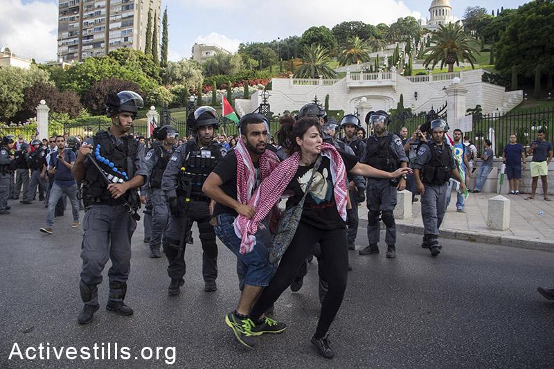 שוטרי מג״ב מנסים לעצור פלסטינים תושבי ישראל במהלך הפגנה נגד המתקפה בעזה, חיפה, ה-18 ליולי, 2014. 28 מפגינים נעצרו על ידי מג״ב. (אורן זיו/אקטיבסטילס)