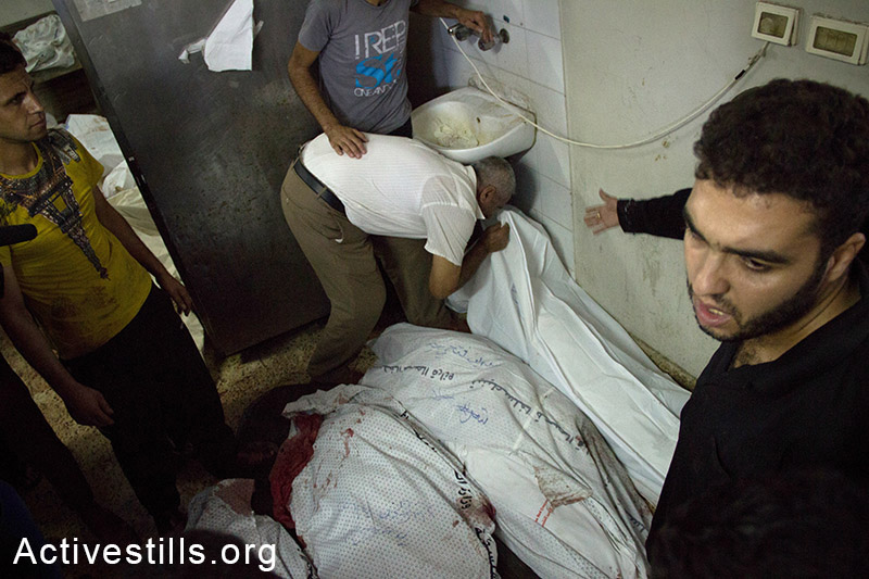 קרוב משפחה מנשק את גופות בני משפחתו בבית החולים אל-שיפא. עזה, ה-20 ליולי, 2014. (אל פאק/אקטיבסטילס)