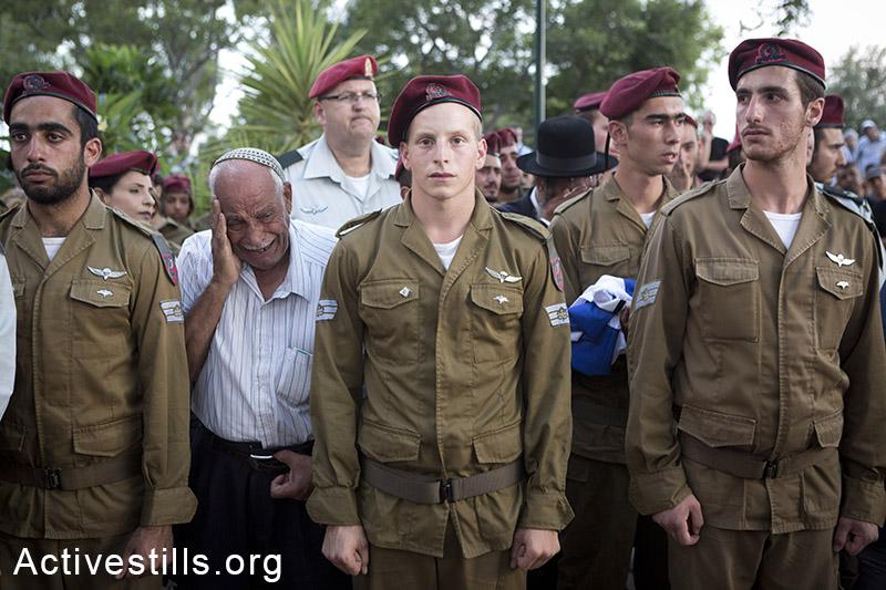 קרוב משפחה מתייפח מאחורי משמר חיילים מפלוגתו של החייל בניה רובן שנהרג במהלך המתקפה הישראלית בעזה. חולון, ה-20 ליולי, 2014 (אורן זיו/אקטיבסטילס)