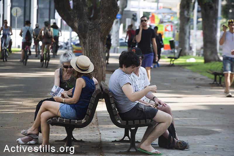 עוברים ושבים מסתכלים בגלויות שחילקו פעילי שמאל הנותנים מידע על המתקפה הישראלית בעזה, תל אביב, ה-22 ליולי, 2014. (קרן מנור/אקטיבסטילס)