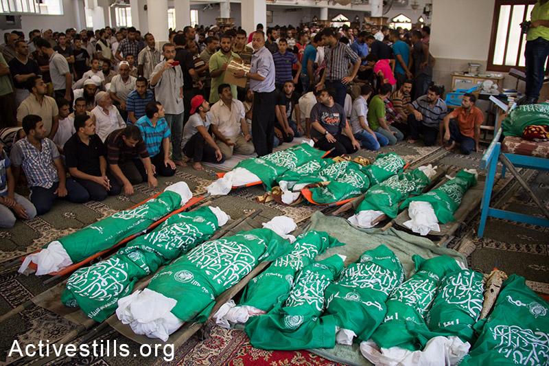26 גופותיהם של משפחת אבו-ג׳אמע שנהרגה בהפצצות הצבא מונחות לפני הלוויתן.  עזה, ה-21 ליולי, 2014. (באסל יאזורי/אקטיבסטילס)