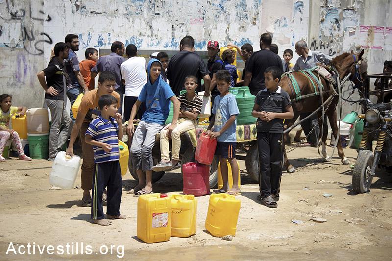 תושבי חאן יונס נאספים סביב באר מים כדי למלא כדי פלסטיק במים ראויים לשתיה. רצועת עזה, 27 יולי 2014. (באסל יאזורי/אקטיבסטילס)