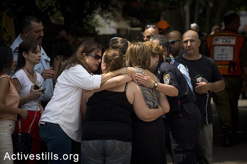 תושבי יהוד מתחבקים לאחר פגיעה ישירה של טיל באזור מגוריהם, ה-22 ליולי, 2014. (אורן זיו/אקטיבסטילס)