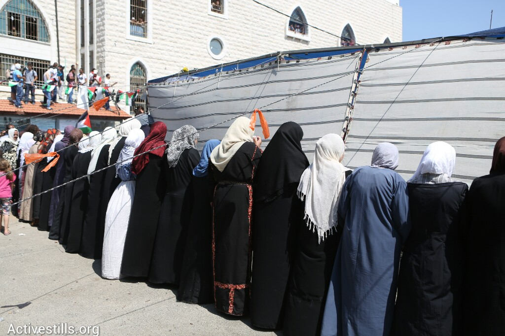 נשים מסתתרות מירי שוטרים ישראלים, בהלווית הנער מוחמד חוסיין אבו-ח׳אדר בשועפט, שנחטף ונרצח על ידי יהודים, מזרח ירושלים, ה-4 ליולי, 2014 (אורן זיו/אקטיבסטילס)