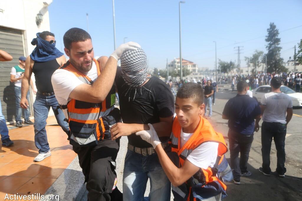 צעיר שנפגע על ידי שוטרים, מפונה על ידי חובשים בהלווית הנער מוחמד חוסיין אבו-ח׳אדר בשועפט, שנחטף ונרצח על ידי יהודים, מזרח ירושלים, ה-4 ליולי, 2014 (אורן זיו/אקטיבסטילס)