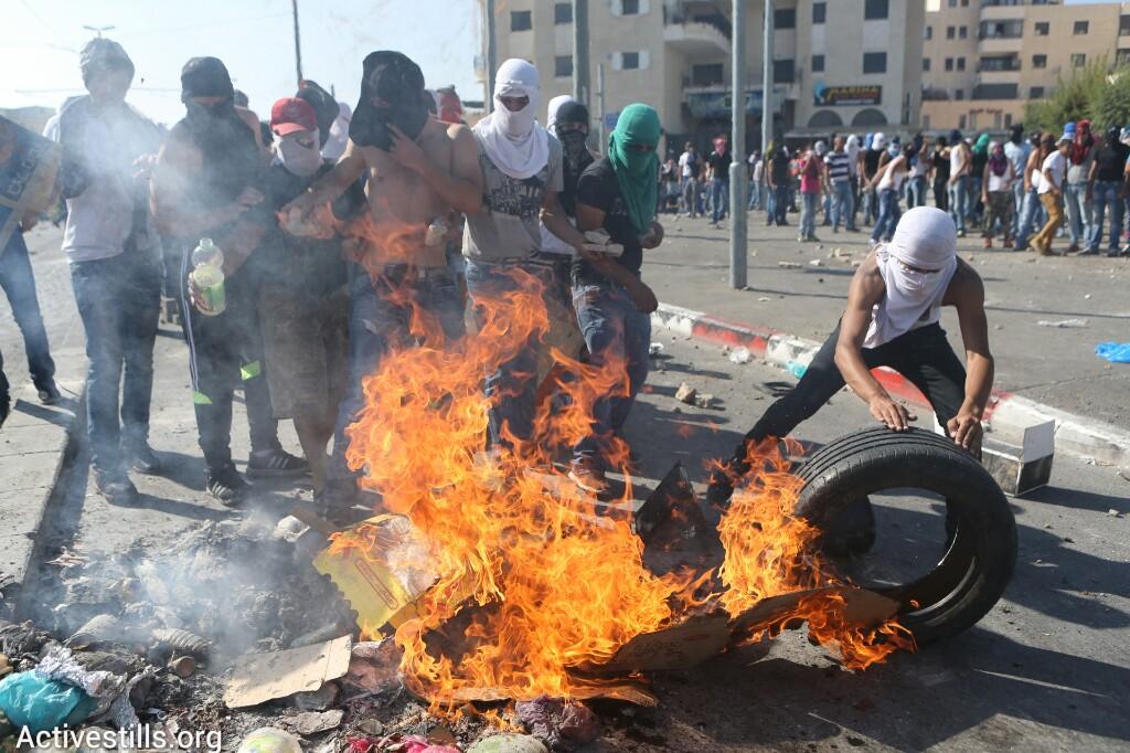 נערים פלסטינים מבעירים צמיגים בהלווית הנער מוחמד חוסיין אבו-ח׳אדר בשועפט, שנחטף ונרצח על ידי יהודים, מזרח ירושלים, ה-4 ליולי, 2014 (יותם רונן/אקטיבסטילס)