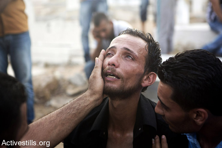 קרוב משפחה של אחד מהילדים שנהרגו במחנה הפליטים אל-שאטי מתאבל במהלך הלוויה, עזה, 28 ליולי, 2014. פיצוץ שארע במחנה הפליטים גרם למותם של עשרה, רובם ילדים, ולפציעתם של כארבעים אנשים. (אן פאק/אקטיבסטילס)