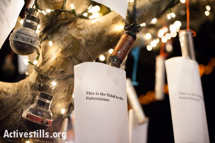 """""""זה הסיוע האמריקאי לפלסטינים"""". רימוני גז משומשים על עץ חג המולד בבית חם (ריאן רודריק ביילר / אקטיבסטילס)"""