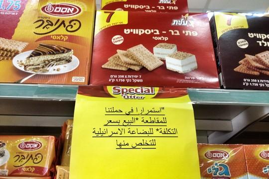"""שלט בכניסה לחנות מכולת ברמאללה: """"בהמשך להשתתפותנו בקמפיין החרם - מכירה במחירי עלות של הסחורות הישראליות, כדי להיפטר מהן"""". (צילום: ג'סיקה דוואני, Just Vision)"""